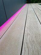 Enhanced grain Smoked Oak Millboard decking detail with RGB colour change LED lighting