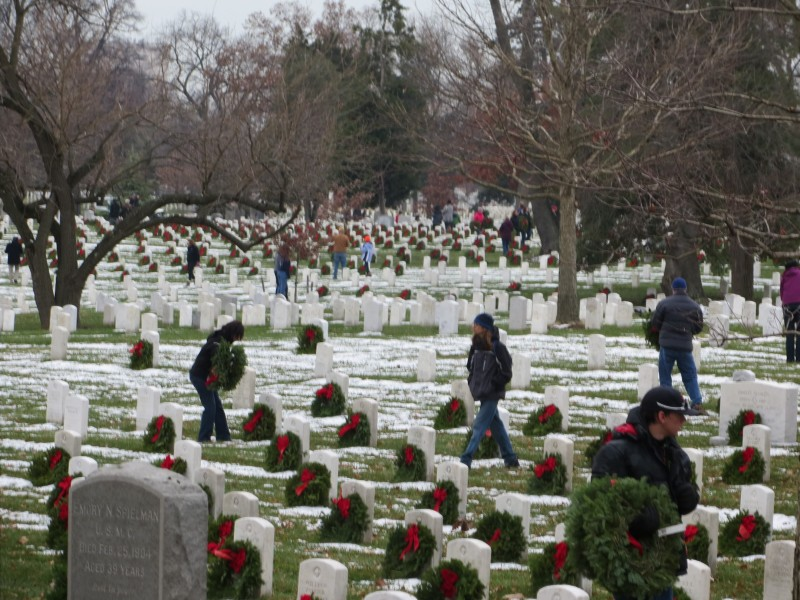 Volunteers look for headstones in their assigned section which still need wreaths.