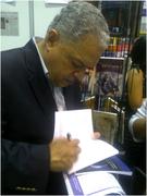 FIRMANDO UN LIBRO EN STAND DE LA FERIA DEL LIBRO DE PANAMA 2012