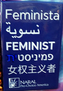 Rectangular dark blue button with white text: Feminista, نسوية, FEMINIST, פמיניסטית [with feminine ending ית blued out], 女权主义者 [Statue of Liberty logo] NARAL Pro-Choice America