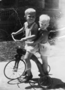 Brothers sharing a tricycle ride