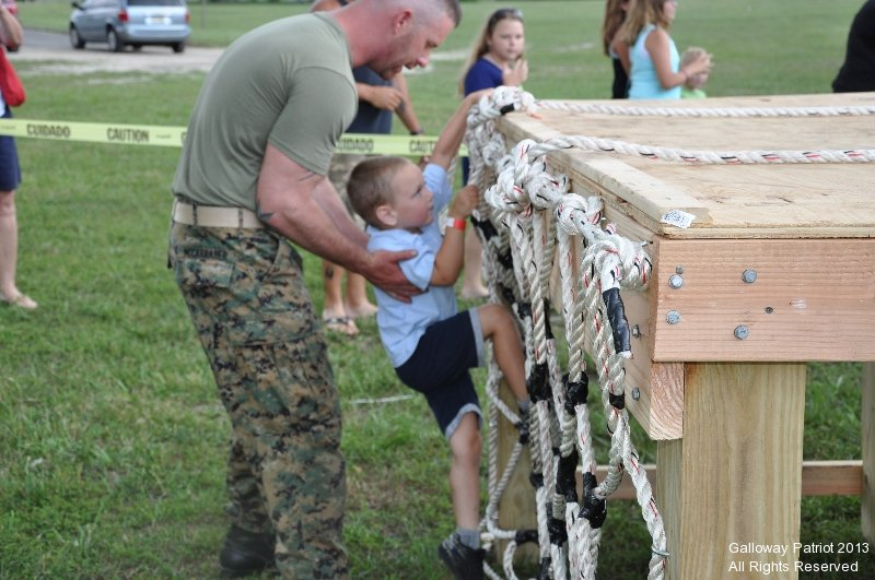 U.S. Marine Joe helps a participant climb the rope net