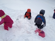 Children enjoying snow, pretending white cold sand.