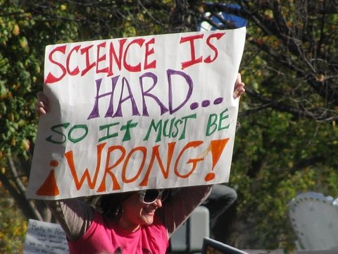 Woman in pink shirt holding up a sign: SCIENCE IS HARD... SO IT MUST BE ¡WRONG!