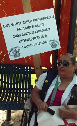 Woman with protest sign: ONE WHITE CHILD KIDNAPPED IS AN AMBER ALERT - 2000 BROWN CHILDREN KIDNAPPED IS A TRUMP AGENDA