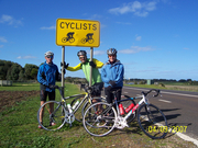 Three Cyclists bythe road sign