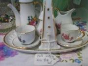 Closeup of white porcelain mini tea set with jewel toned rose bouquets
