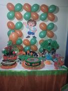 la decoracion de la mesa, con la chupetera, arboles, galletas, gelatina y torta.