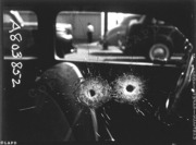 Detail of two bullet holes in car window (LAPD archives)
