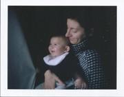 La felicità è una bimba che gioca con la tenda tra le braccia amorevoli della mamma
