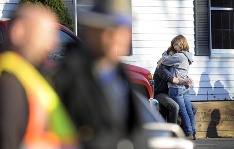People embrace at a firehouse staging area for family near the scene of a shooting at the Sandy Hook Elementary School in Newtown, Conn. where a gunman opened fire, leaving 26 people dead, including 20 children, Friday, Dec. 14, 2012. (AP Photo/Jessica Hill)