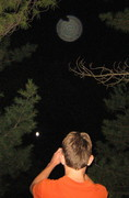 Boy takes picture of full moon, while other orb watches edit
