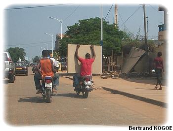 Il transporte un contreplaqué sur la moto