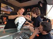 Robby and Max Gordon signing a helmet for James Walton