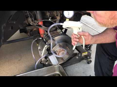 Bleeding brakes with a vacuum pump.