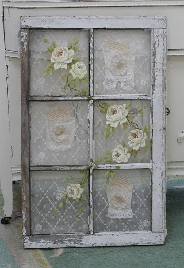 Vintage lace was added to the back of this old window while pretty roses were painted on the front. Gorgeous reuse!