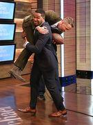 Michael Strahan holding Ryan Reynolds