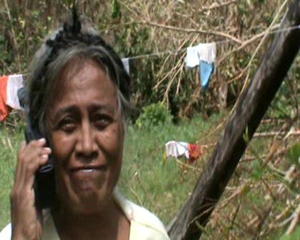 Nei Mere Eritabeta talking on satellite phone with children Suva