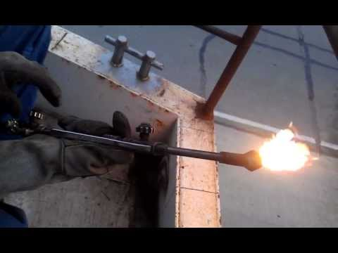 Carl Kelley ignites an oxy-acetylene cutting torch.