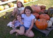 Girls sitting with heirloom pumpkins