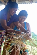 An elder teaches a younger woman how to weave