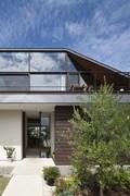 Moderní dům s prosklenou valbovou střechou