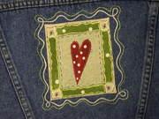 Embellished fabric square on denim jacket