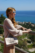 Bea Conesa is wearing Arantxa Bag in beige and piton with a pastel pink look in front of the Mediterranean sea