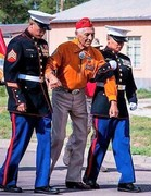 Two young Navajo Deckarated Marimes helping USMC Roy Hawthorne Former Navajo Code talker finish a prade