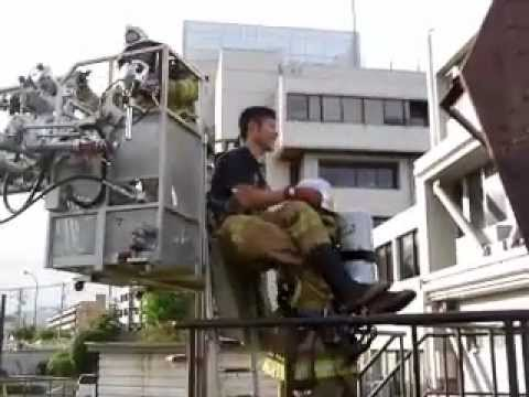 Japanese firefighter training how to put a victim into a ladder bucket