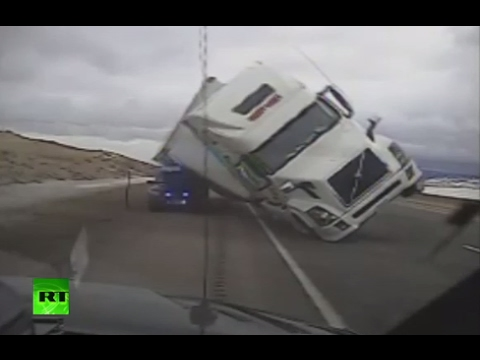 Strong wind sends truck toppling onto patrol car in US