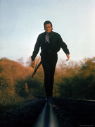 michael-rougier-country-music-star-johnny-cash-walking-along-line-of-railway-track-with-his-guitar