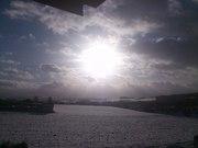 Brilliant White Sun against a cloudy dark sky