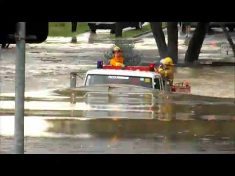 Camión de bomberos atraviesa camino inundado