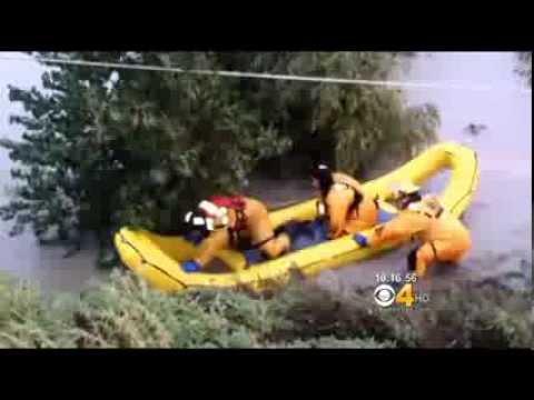 rescatistas  salvan personas en autos arrastrados por una inundación