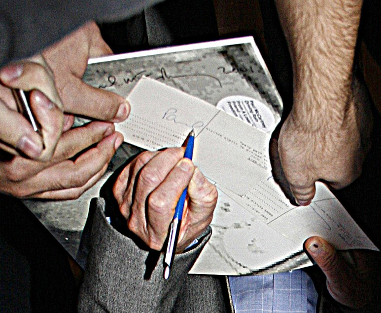 Paul signs for me on a postcard - enlargement