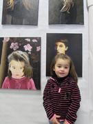 Ines devant son portrait lors d'une exposition à Dinan