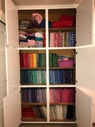 Quilting stash organized!  Precuts are stored in small bins or ziplock bags. Yardage is folded onto comic book boards. Books and patterns still need to go on bookshelves. Notions in rolling cart. Seve