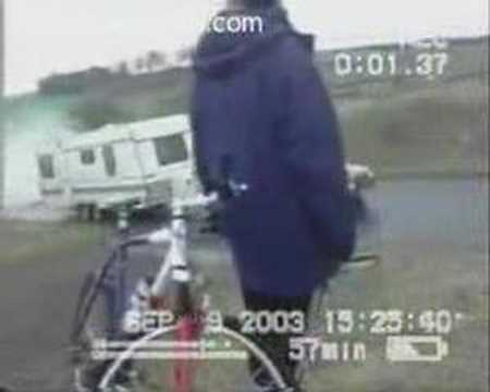 Bicyclists watch car and trailer roll down hill