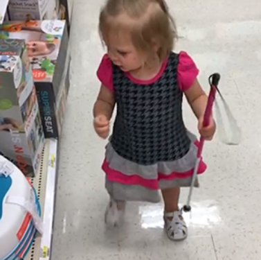 toddler-aged girl in dress walking down aisle of store holding cane