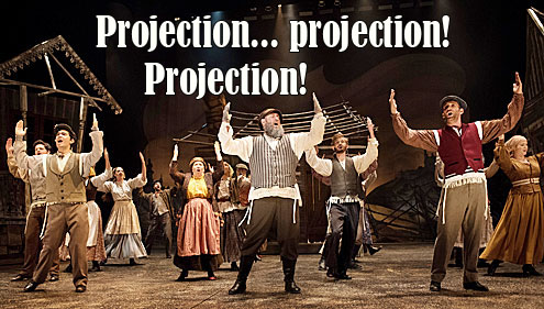'Projection... projection! Projection!' (caption over scene from Fiddler on the Roof, with Tevye and other characters singing 'Tradition!')