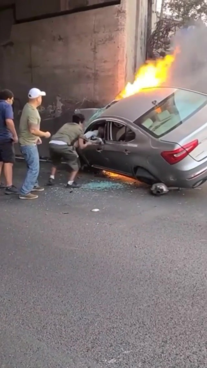 People help a man get out of a burning car