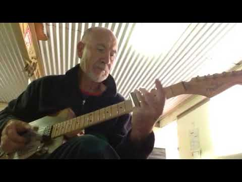 Taffy Evans testing an early cigar box guitar